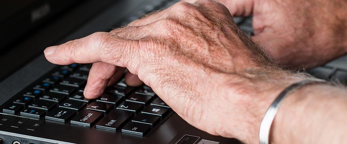 Hände tippen auf Laptop